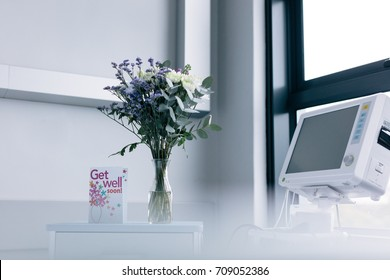 Get well soon wishing card with flower vase on side table in hospital room.