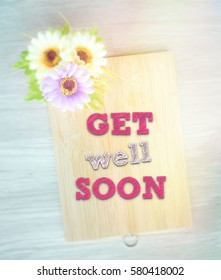get well soon words on the wooden background vintage retro or rustic style with flowers