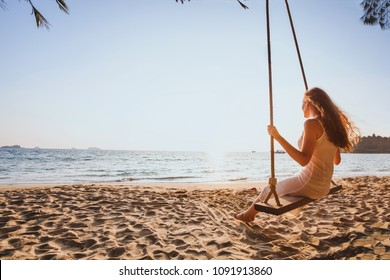 getaway dream and happiness concept, romantic beautiful carefree woman relaxing on the swing at sunset beach, summer holidays, vacation travel and relaxation, inspiring landscape