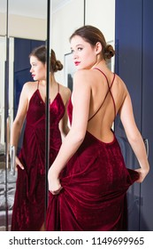 Geting Ready for a Night Out - Beautiful young woman in red dress with naked back, standing in front of the mirror, beauty fashion concept