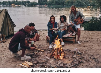 Getting away from it all... Group of young people in casual wear smiling while enjoying beach party near the campfire
