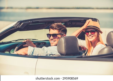 Getting away on weekend. Cheerful young couple smiling at camera while riding in their white convertible