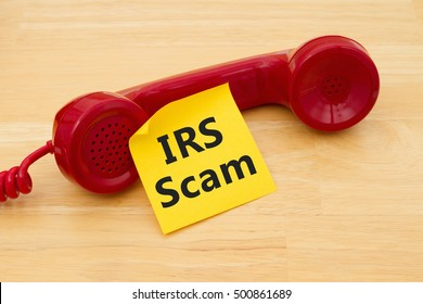 Getting a call that is an IRS Scam, A retro red phone with yellow sticky note on a desk with text IRS Scam
