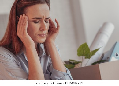 Getting detached. Close up of young stressed woman keeping her eyes closed while touching her temples and experiencing disappointment