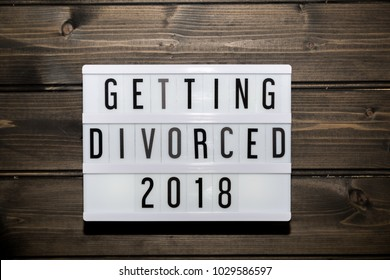 getting divorced 2018 message in light box, grunge wood table flat lay shot from above