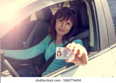Getting a driver's license, a beautiful driving girl shows a new driver's license