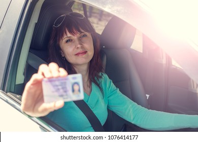 Getting a driver's license, a beautiful driving girl shows a new driver's license, Cars with left-hand traffic