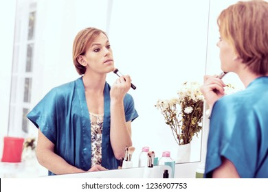 Getting face ready. Attractive ginger short-haired gender-queer applying foundation with makeup brush staying in his beauty room