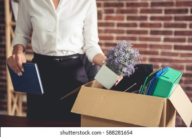 Getting fired. Cropped image of beautiful young business woman in formal wear packing her stuff into the box