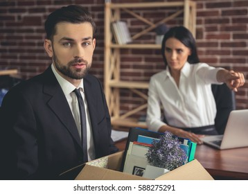 Getting fired. Handsome businessman in suit is holding a box with his stuff, woman in the background is pointing away