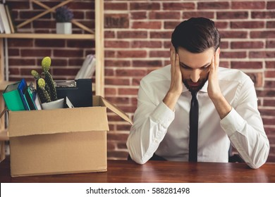 Getting fired. Handsome businessman in suit is sitting sadly at the table in office near the box with his stuff