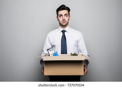 Getting fired. Handsome businessman in suit in office with the box with his stuff