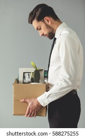Getting fired. Side view of handsome businessman in formal wear holding a box with his stuff, on gray background