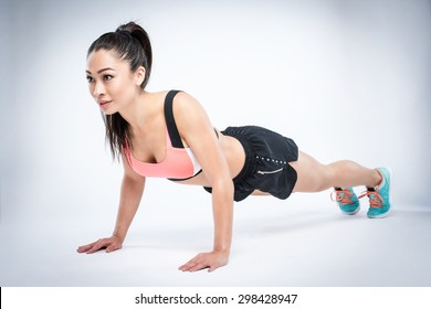 Getting fit with press ups. Studio shot with beautiful mixed race Asian girl.