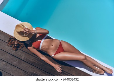 Getting golden tan. Full length top view of beautiful young woman in swimwear covering face with hat while sunbathing by the pool
