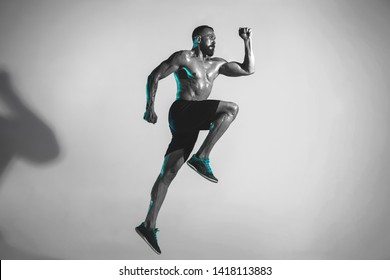 Getting higher than bird. Young caucasian bodybuilder training over studio background in neon light. Muscular male model jumping. Concept of sport, bodybuilding, healthy lifestyle, motion and action.