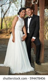 Getting married young hispanic couple holding hands together on park background