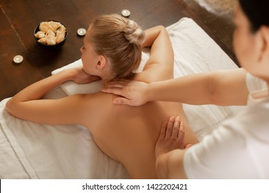 Getting massage. Calm woman with fit body lying on a covered bed in equipped cabinet and getting her back massaged
