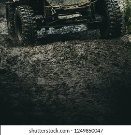 Getting the most out of the off road adventure. Car wheels on steppe terrain splashing with dirt. Car racing offroad. Offroad car in action. Dirty car drive on high speed. SUV offroader on mud road.