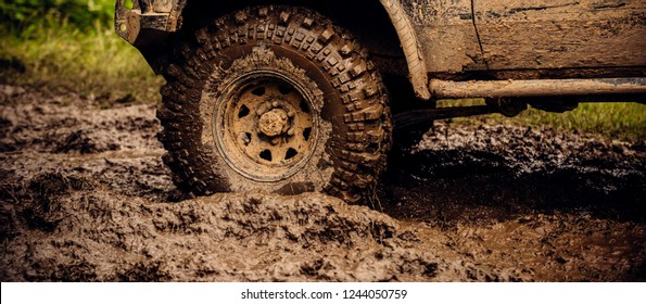 Getting off the beaten path. Car wheels on steppe terrain splashing with dirt. SUV or offroader on mud road. Car racing offroad. Offroad car in action. Dirty car drive on high speed.