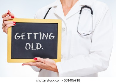 Getting Old Chalkboard Sign Held By Female Doctor.