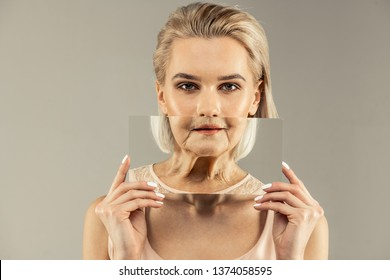 Getting old. Pleasant nice woman holding a mirror while imagining her future look