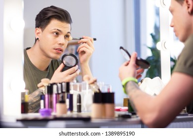 Getting ready. Attentive dark-haired man carrying container with powder and adding it on the face