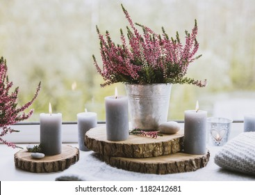 Getting ready for autumn. Cozy autumn set on window sill. Gray candles, flame wooden boards, common pink heather flower in zinc bucket flower pot. Cozy living space concept.
