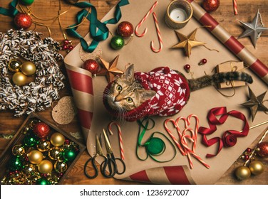 Getting ready for Christmas or New Year holiday. Flat-lay of decorations, ribbons, gift paper, door wreath, glittering balls, candy canes and cat in Christmas sweater ,top view. Christmas festive mood