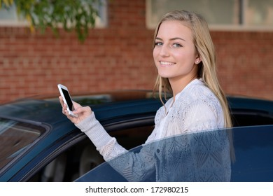 Getting Ready to Drive. Young woman getting in to a car while holding a smartphone.