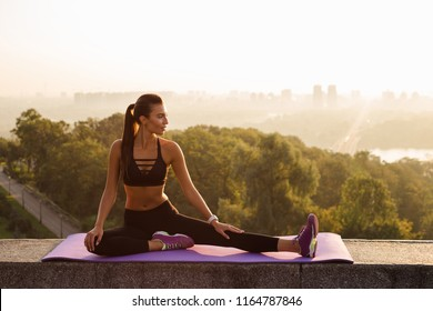 Getting ready for a intensive workout. Full length of young beautiful fit woman in sportswear doing stretching while sitting against industrial city view