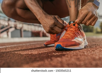 Getting ready to jogging. Close up shot of hands tying shoelaces sneaker on the running track