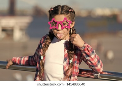 Getting ready for party. Small naughty girl having fun. Fashionable glasses for celebration. Stylish look. Disobedient small girl showing her tounge. Positive moments. Concept of childish carelessness