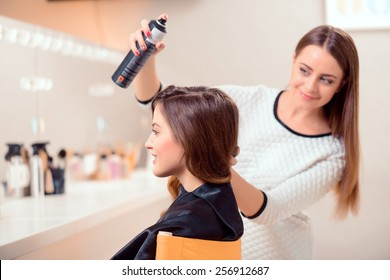 Getting ready for the runway. Side view of a young beautiful woman sitting in hair salon and looking into the mirror while her hairdresser getting her hair done with hair spray