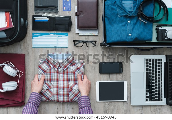 Getting ready for a trip and packing a suitcase, a man is holding his shirt before putting it into his bag, travel and vacations concept