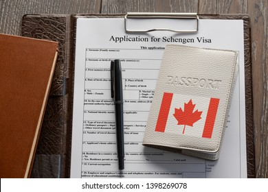 Getting a Schengen visa. Application form, pen and a Canadian passport. Travelling to Europe.