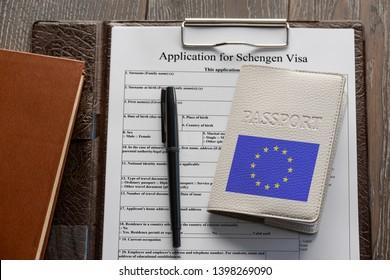 Getting a Schengen visa. Application form, pen and European Union passport. Travelling to Europe.