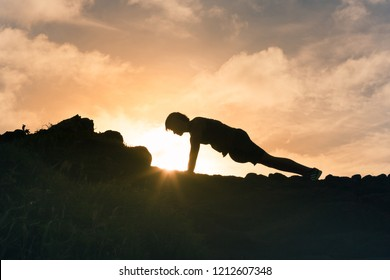 Getting in shape feeling motivated. Young man doing pushup exercise outdoors.