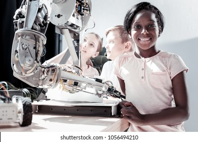 Getting smarter every day. Waist up shot of an African American girl looking into the camera with a cheerful smile on her face after visiting a work shop and seeing impressive robotic machines.