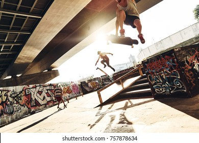 Getting some air. Three young men skateboarding at the skate park together