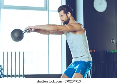 Getting stronger every day. Side view of young handsome man in sportswear working out with kettle bell at gym
