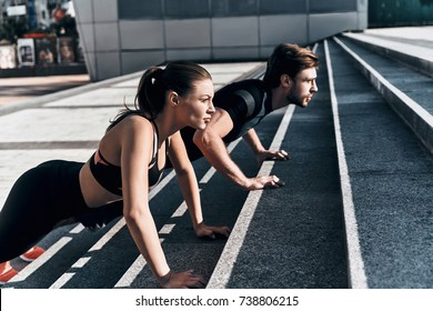 Getting stronger. Young couple in sport clothing doing push-ups while exercising on the stairs outdoors