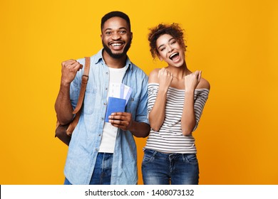 Getting Visa. Lucky Couple Holding Flying Tickets Over Yellow Background