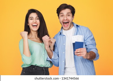 Getting visa. Lucky couple showing passports with flying tickets over yellow background
