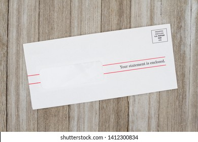 Getting your bill, A white envelope on weathered wood with text Your statement is enclosed