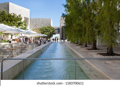 Getty Center, Los Angeles, California - September 2018. Patrons and visitors enjoy the cafe next to a water feature fountain in the courtyard at the Getty Center and Museum on a warm afternoon.