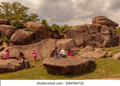 Gettysburg, PA, USA - July 8, 2013:  Visitors at Devil's Den on the Gettysburg Battlefield lounge on boulders used artillery and infantry on day two of the 1863 Battle during the American Civil War.