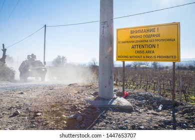GEVGELIJA, MACEDONIA - DECEMBER 23, 2015: Macedonian army tank passing in front of a roadsign indicating the border with Eidomeni/Idomeni in Greece is closed, due to refugees crisis on balkans route
