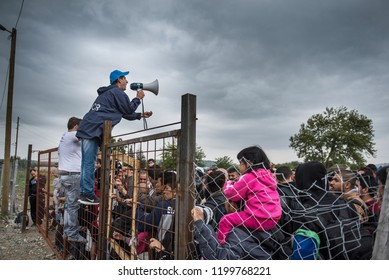 Gevjelija, Macedonia - September 26, 2015. A UNHCR employee talks to refugees as they wait during a rainstorm to enter inside a refugee camp near the town of Gevgelija at the Macedonian - Greek border