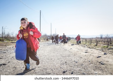 GEVLGELIJA, DECEMBER 23, 2015: Young refugee child carrying heavy backpack on the Greece Macedonia border, between cities of  Eidomeni Idomeni & Gevgelija on the Balkans Route, during Refugee Crisis